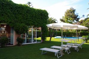 Der Garten der Villa mit Pool und Sonnenliegen