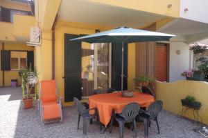 Terrasse mit Grill, Esstisch, Sonnenschirm und Sonnenliegen